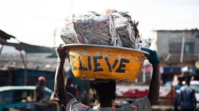 Image of a man carrying Slabs of frozen fish from Saiko making its way to the market.